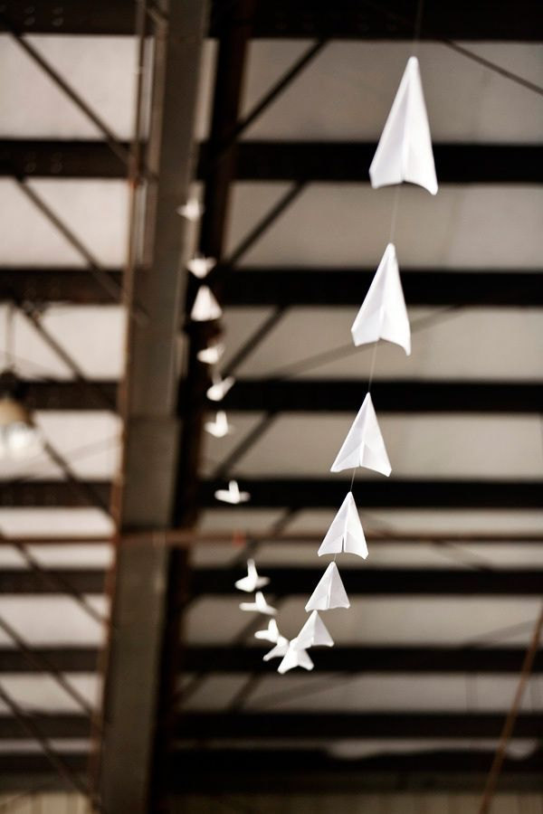paper airplane garland - cheap and easy way to theme - could look really cool zigzagged up high along the beams