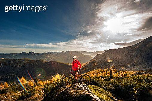 Austria, Altenmarkt-Zauchensee, young man with mountain bike at Low Tauern - gettyimageskorea   #게티이미지코리아 #gettyimageskorea #게티이미지  #Experience #leisure #sports #레저활동#사이클링 #산악자전거 # 산악자전거타기 #선글라스 #스포츠 # 이륜자전거