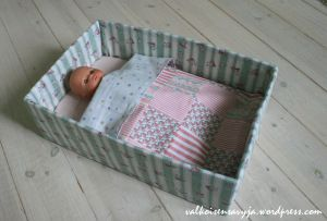 Doll's bed from a cardboard box with a quilt.