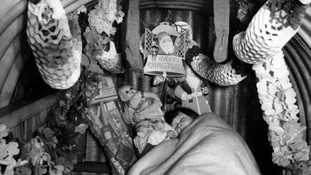 A child sleeps in an air-raid shelter festooned with Christmas decorations – a not uncommon sight in December 1940.
