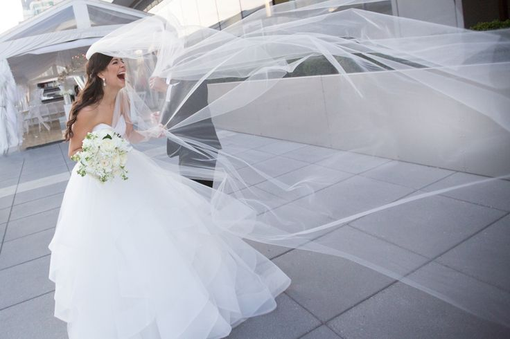 Bride's cathedral length veil blowing in the wind on the rooftop at Malaparte Terrace