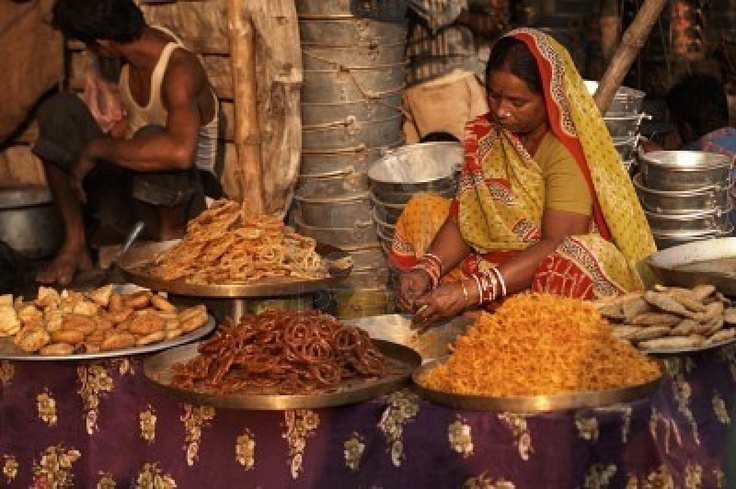 Sonepur, Bihar, India - November 28, 2007: Woman in brightly colored sari selling indian sweets from a market stall at the Sonepur Mela in Bihar, India.  Stock Photo