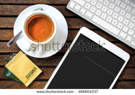 workplace with tablet computer showing magazine cover and a cup of coffee on a wooden work table close-up, over light