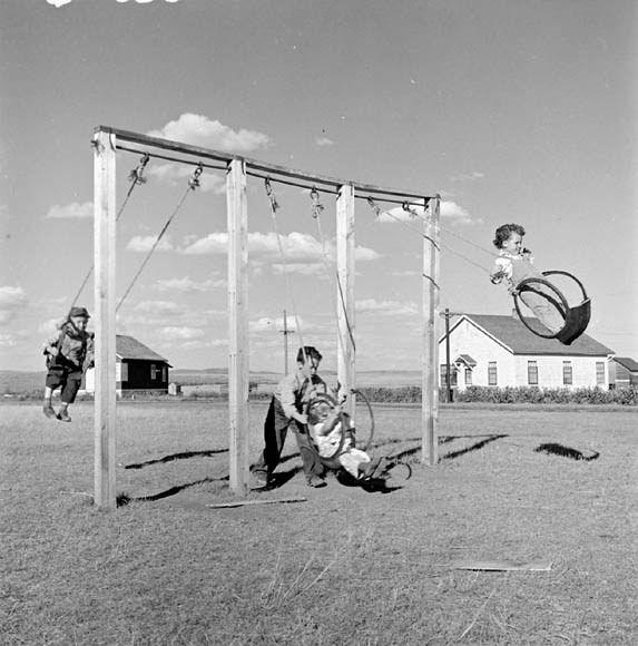 Children playing on swings made from old truck tires on the Matador Co-operative Farm / Des enfants font de la balançoire sur de vieux pneus à la ferme coopérative Matador | by BiblioArchives / LibraryArchives