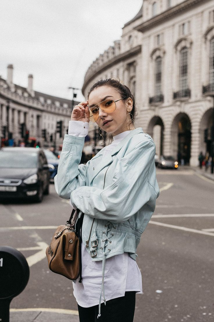 Fashion blogger Beatrice Gutu wearing corset trend with white shirt, lace up leather jacket and yellow tinted sunglasses during London Fashion Week