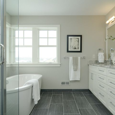 White Vanity, long dark grey tiles, nice deep tub. Very clean looking.