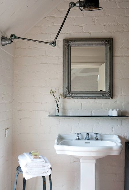 simplicity - exposed brick wall in the bathroom with vintage lighting and pedestal sink