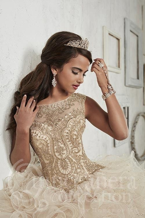 Glimmering embroidery dipped in gold and wavy tulle flecked in sparkle like stars across a skirt canvas, with an embroidered illusion neckline and straps. Download the Quinceanera Collection by House