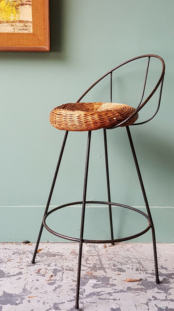 Fantastic style on this wrought iron back & legs bar stool with wicker rattan wocen seat. Some wear on seat but completely usable as is. Great design but no identifying marks. 27.5 seat hwight and 36 Inches to top of seat back.   Shipping will be with Greyhound Station to Station. If you need to door delivery there is an extra chairge with Greyhound Package Express. Please feel free to ask questions.