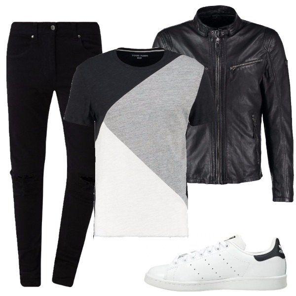 Outfit composto da t-shirt resa particolare dalla presenza di blocchi di diversi colori, giubbotto in pelle nera con collo alla coreana, jeans nero e sneakers bianche.