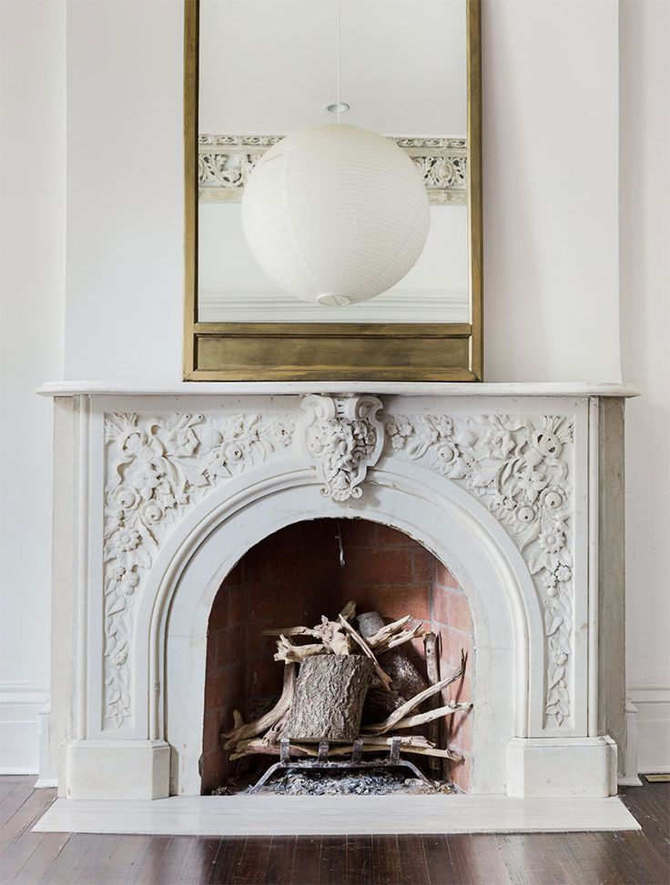 An all-white fireplace with a gold mirror and white lamp. So minimalistic and…