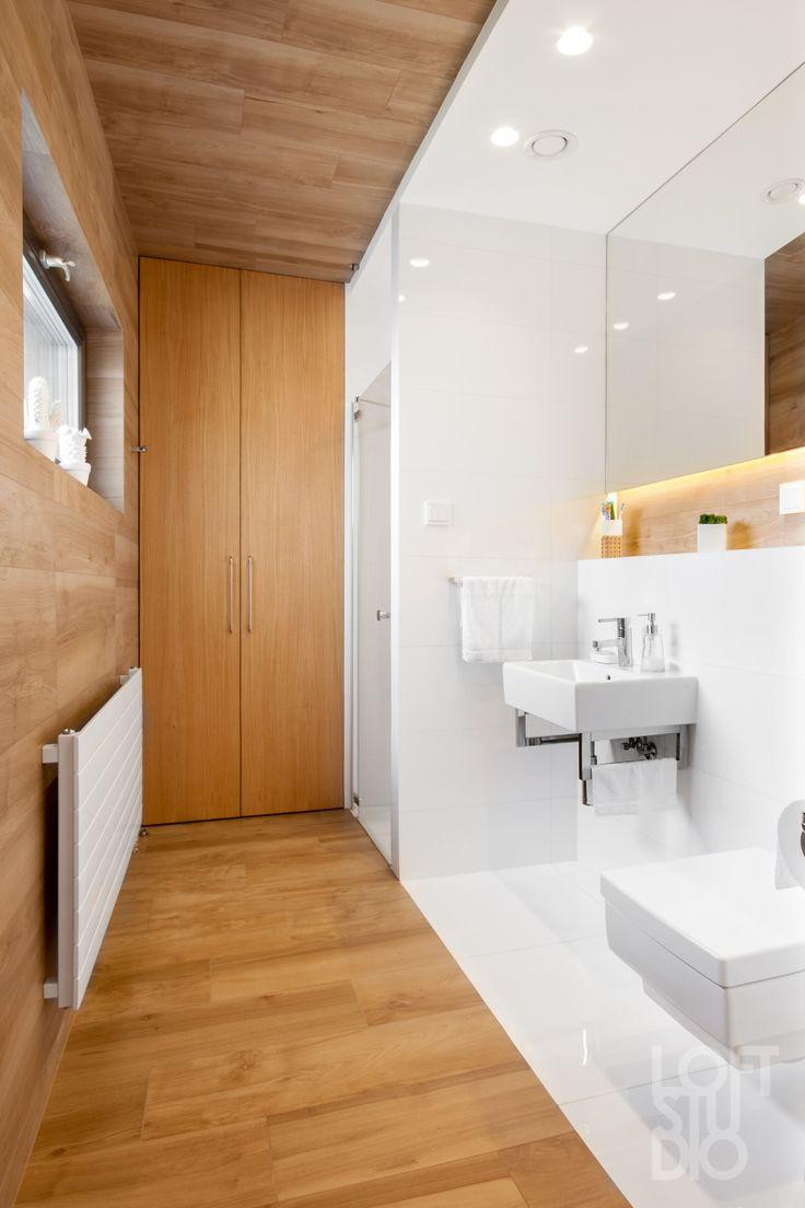 white heater in bathroom design by LOFTSTUDIO/ biały grzejnik na tle drewnopodobnych płytek  w projekcie LOFTSTUDIO Pragniesz podobnego wnętrza to zgłoś się do nas www.loftstudio.pl