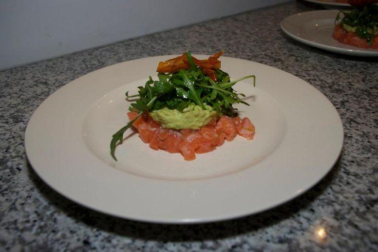 Zalm tartaar met avocdo, rucollo aangemaakt met limoen, dille en olijf olie. gegarneerd met een chipje van tomaat
