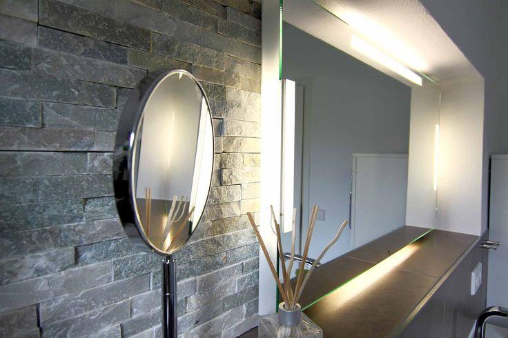 Komsetikspiegel vor Natursteinverbelung in 3D, dahinter großer beleuchteter Spiegel vor der Natursteinwand im Bad angebracht