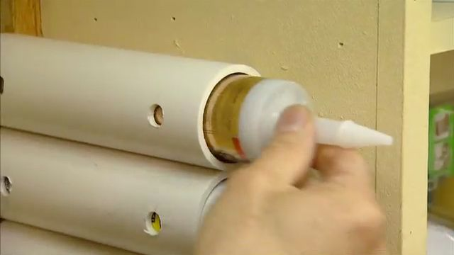 """pvc pipe caulking tube storage (Cut pieces of 2"""" inside diameter PVC pipe 8"""" long. Drill two sets of holes straight through the pipe to fit a flathead screw.)"""