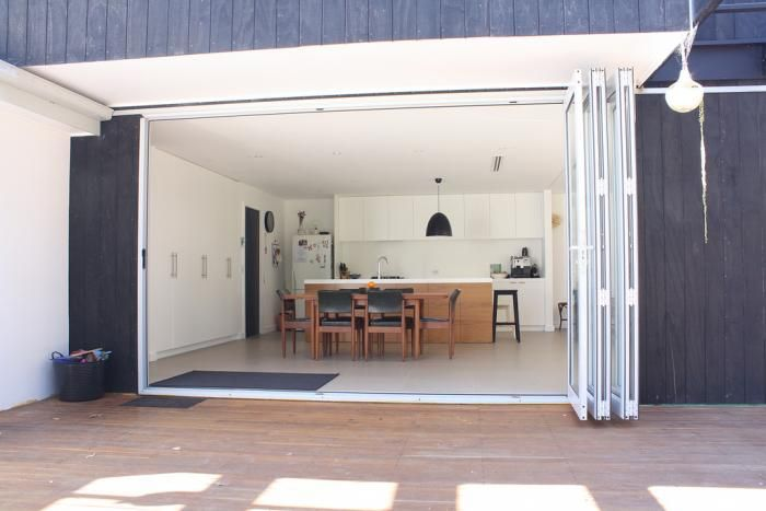 Apres-renovation: folding doors create a seamless flow behind the indoors and the outdoors. With the help of family, Melissa and Damian laid the concrete slab foundation for the addition themselves. Then Damian hired a carpenter friend to help him frame t