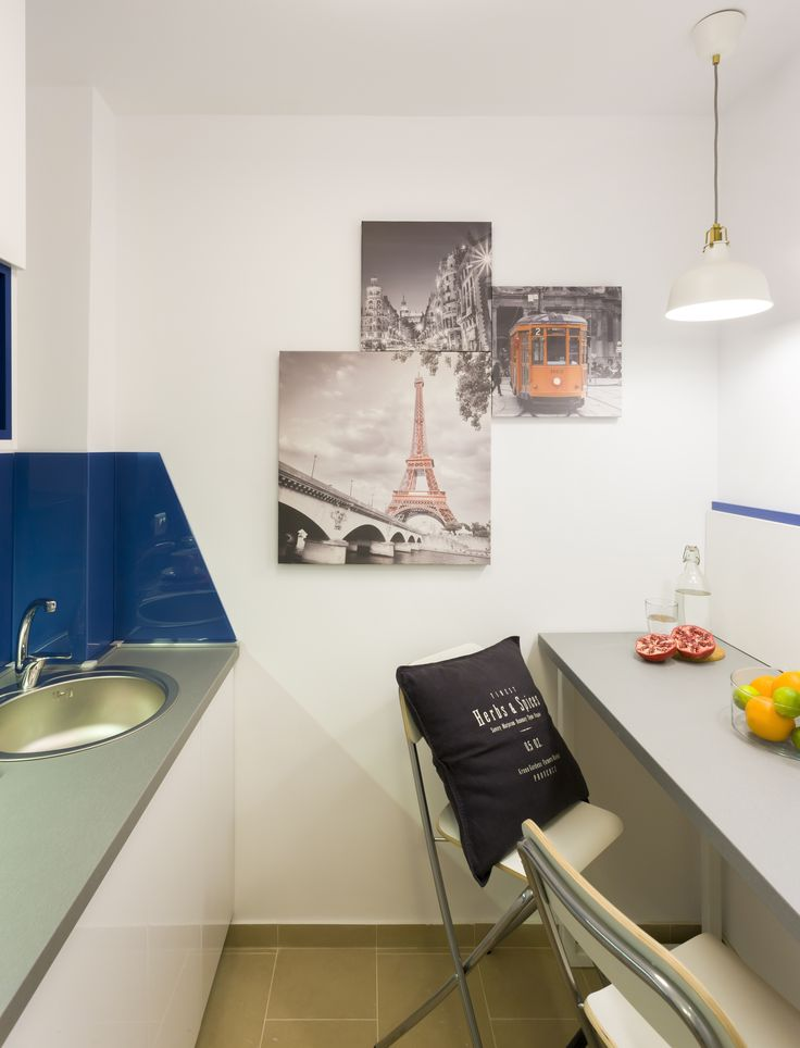 Small kitchen design, with customized printed canvas, white furniture and blue back glass.