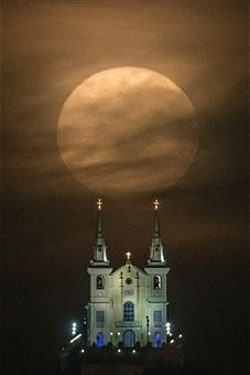 The full moon descends behind the Nossa Senhora da Penha Church in Rio de Janeiro, Brazil, on August 10, 2014. In this time of the year the orb is at the closest point to the earth. Experts name this phenomenon the supermoon or perigee.