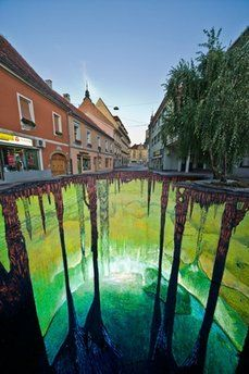 sidewalk artist paints on the concrete to look like you'll fall right in