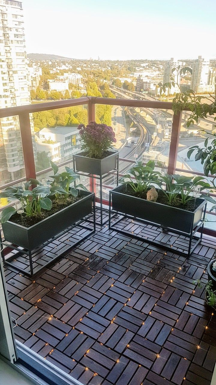 Ein weiterer Balkon einer Stadtwohnung mit Ikea-Deckfliesen, zwischen denen Lichterketten verflochten sind
