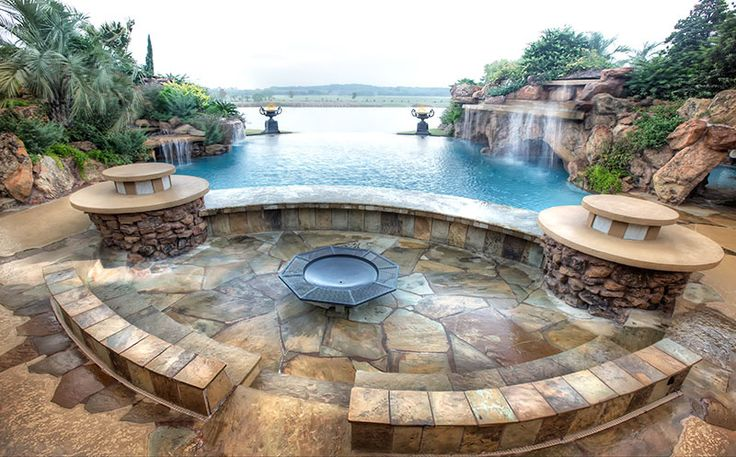 Infinity pool with rock waterfalls stone seating area for Waterfall seat design