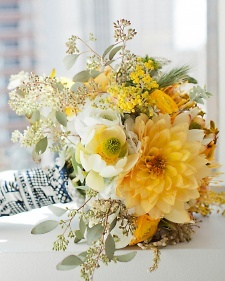 Gathered bouquet of acacia, seeded eucalyptus, pincushion protea, dahlias, ranunculus, daffodils, anemones, sweetpeas, jasmine, star of Bethlehem, leucadendron, kangaroo paws, pieris Japonica, and craspedia.
