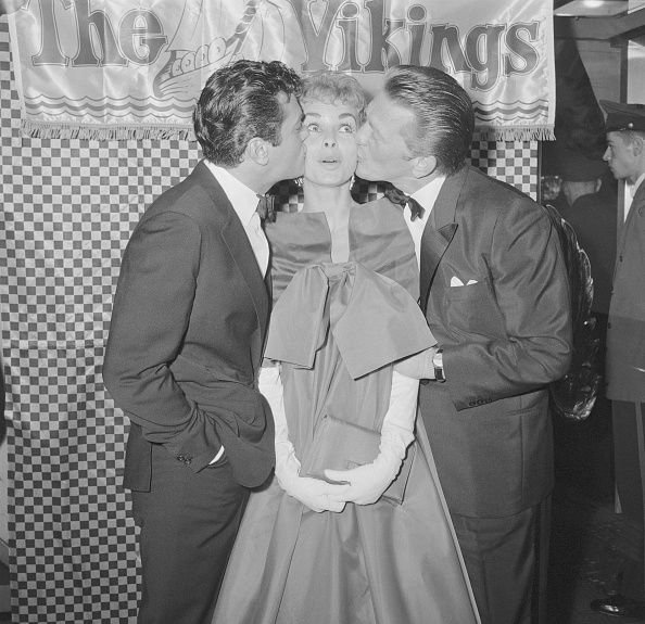 (Original Caption) Caught in a two-way smackup, Janet Leigh get plenty of lip from husband Tony Curtis (L) and Kirk Douglas. The three stars smooched while making personal appearances in two adjoining New York theatres where their new movie The Vikings was premiered simultaneously. Proceeds from the event benefited the Crown Princess student exchange between the US and Norway.