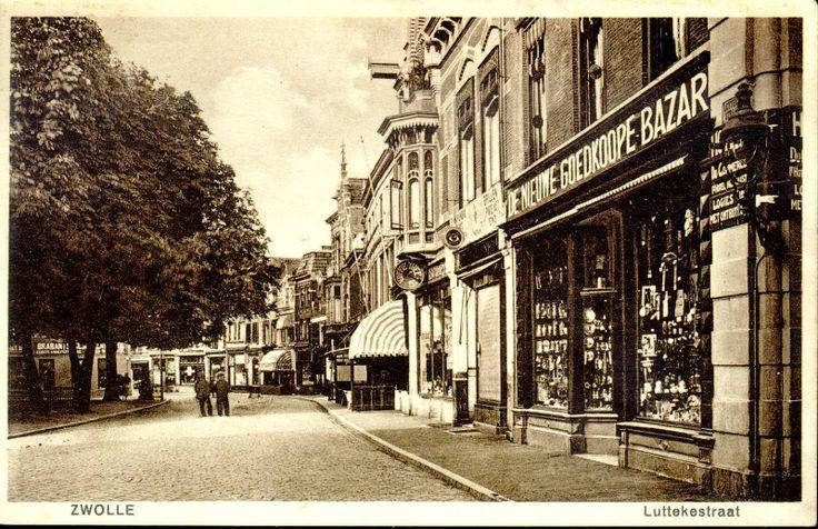 De Luttekestraat vanaf de hoek met de Voorstraat. Rechts op nr. 2 de Nieuwe Goedkoope Bazar van Van Oers. Op de hoek een verwijzing naar Hotel Du Commerce van H.A. van Doorn op Voorstraat 1 (vanaf 1896 koffiehuis). Van 1931 tot 1960 was de zaak in handen van de familie Van Kuik. Op nr. 4 de brillenzaak van Herman Heukels met een oog als uithangbord en boven de etalage de tekst 'Vakkundig oogonderzoek, brillen pincenez enz.' Daarnaast (nr. 4-1) de winkel van de Unie-Maatschappij (een…