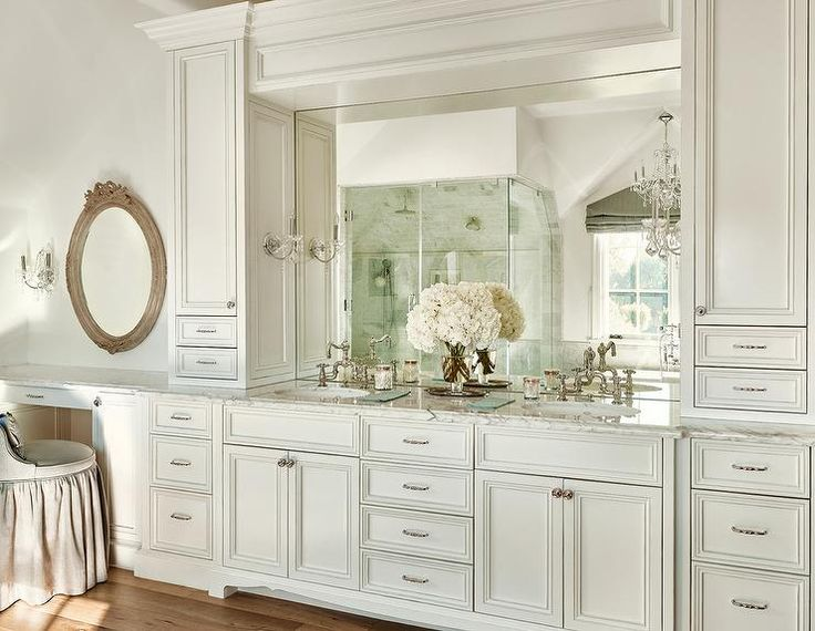 Sophisticated bathroom features ivory cabinets accented with raised panel doors fitted with his and hers sinks and deck mount faucets under a frameless mirror illuminated by glass 1 light sconces flanked by tall cabinets.