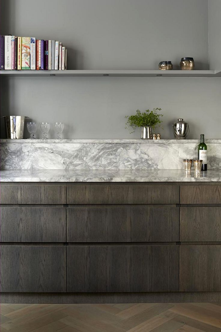 Marble shelf in kitchen. Dark kitchen units and grey open shelves.