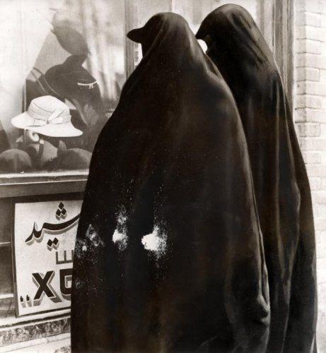 Rasverbroedering, emancipatie, westerse invloeden. Oud Perzië en modern Iran: gesluierde vrouwen in burka of burqa, kijken naar westerse hoeden door een etalage van een winkel in Teheran, Iran 1941.