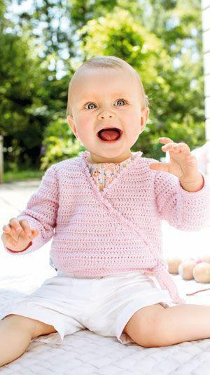 Den søde, hæklede slå om-trøje til baby er hæklet i lutter stangmasker. Trøjen, der er kantet med picot langs forkanterne, lukkes med en knap indvendigt i den ene side og bindebånd i den anden side.