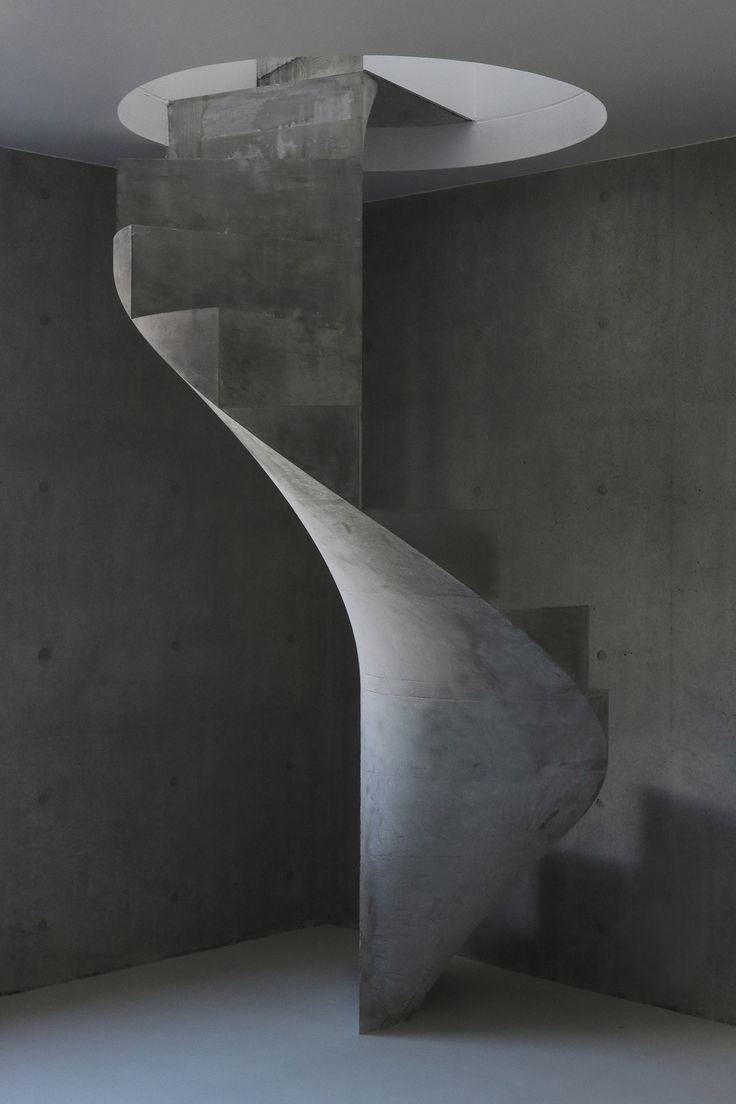 A concrete staircase spirals between the austere concrete floors of this house designed by Kazunori Fujimoto for a seaside spot in Hiroshima