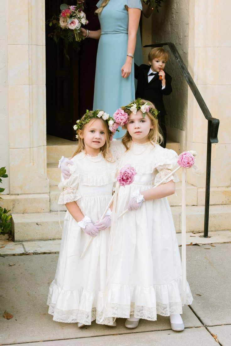 flower girls in vintage lace dresses and gloves wear lush flower crowns of pink peonies, roses and ranunculus and hold flower wands of ivory ribbon and pink peonies.
