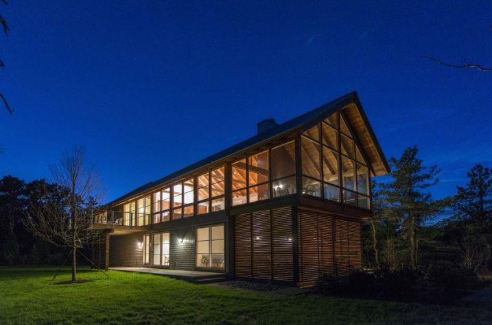 Ce cottage contemporain en bois de deux étages se compose de quatre chambres, il est située le long d'une crête entourée d'une forêt dense.