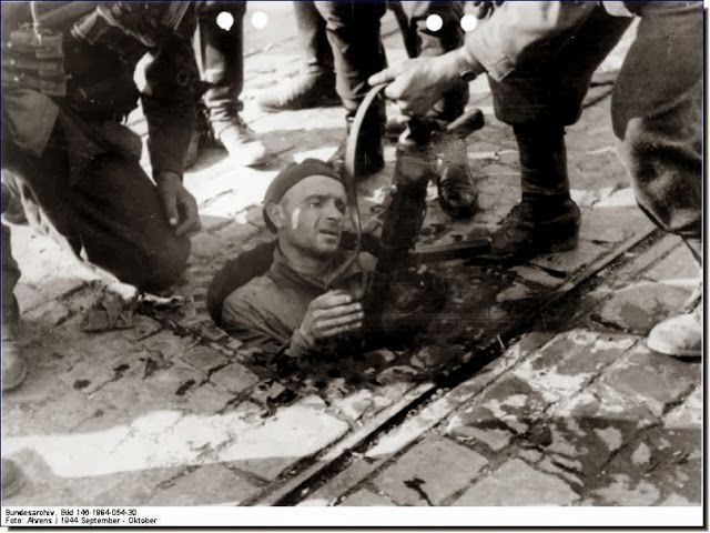 Germans pull out an Armia Krajowa man from a man hole where he was hiding.