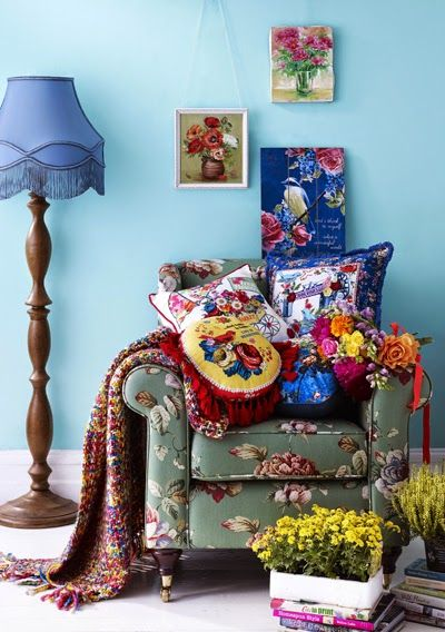 Colourful floral armchair, cushions and pictures