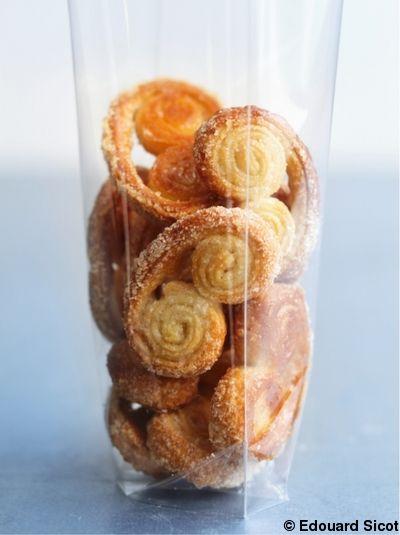 Recette Palmiers    : Saupoudrez le plan de travail de la moitié du sucre. Déposez le rouleau de pâte feuilletée dessus. Saupoudrez le dessus de la pâte av...