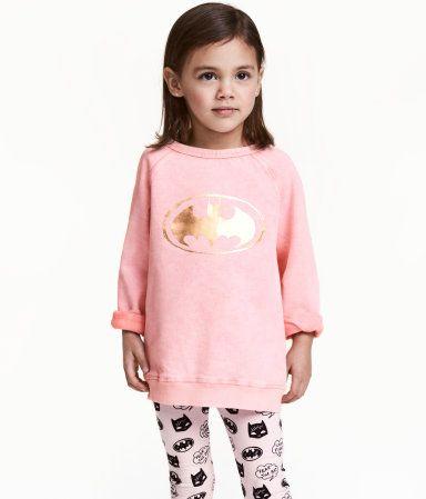 Rosa/Batman. En tröja i mjuk sweatshirtkvalitet med tvättad look. Tröjan har metallicskimrande tryck fram och raglanärm. Mudd kring halsringning, vid