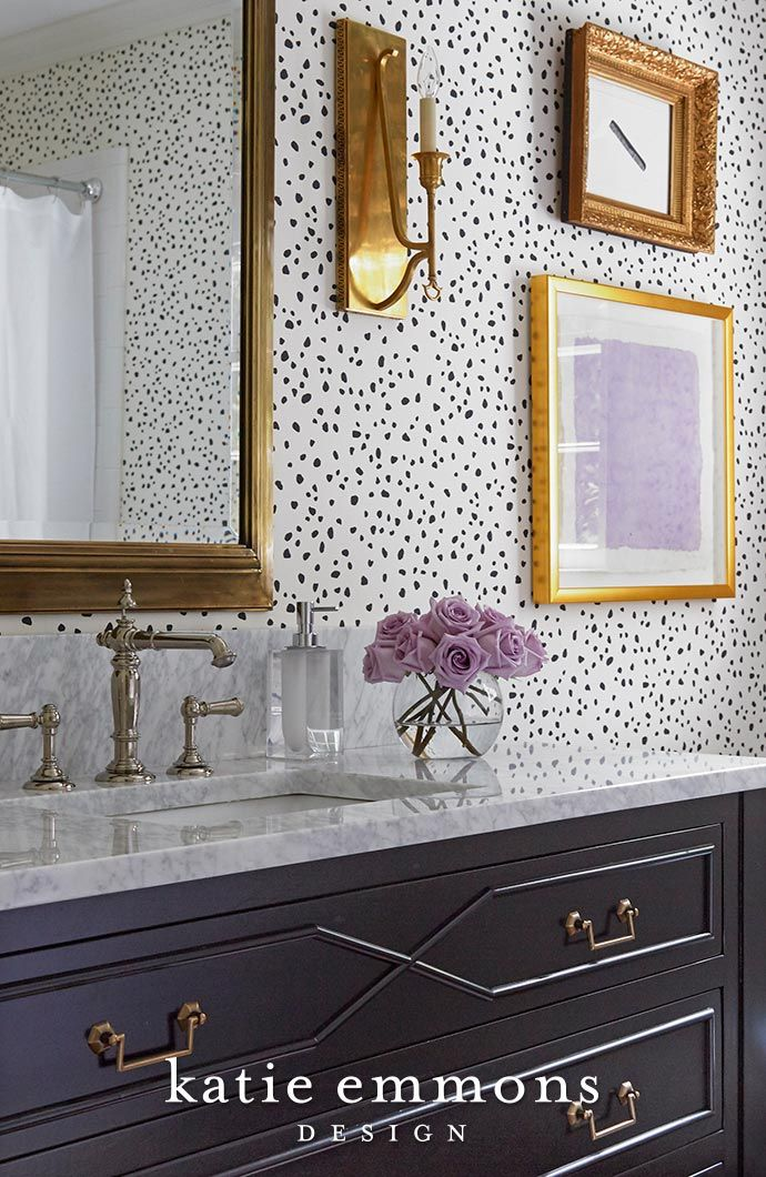 Fun bathroom design featuring gold accents and patterned
