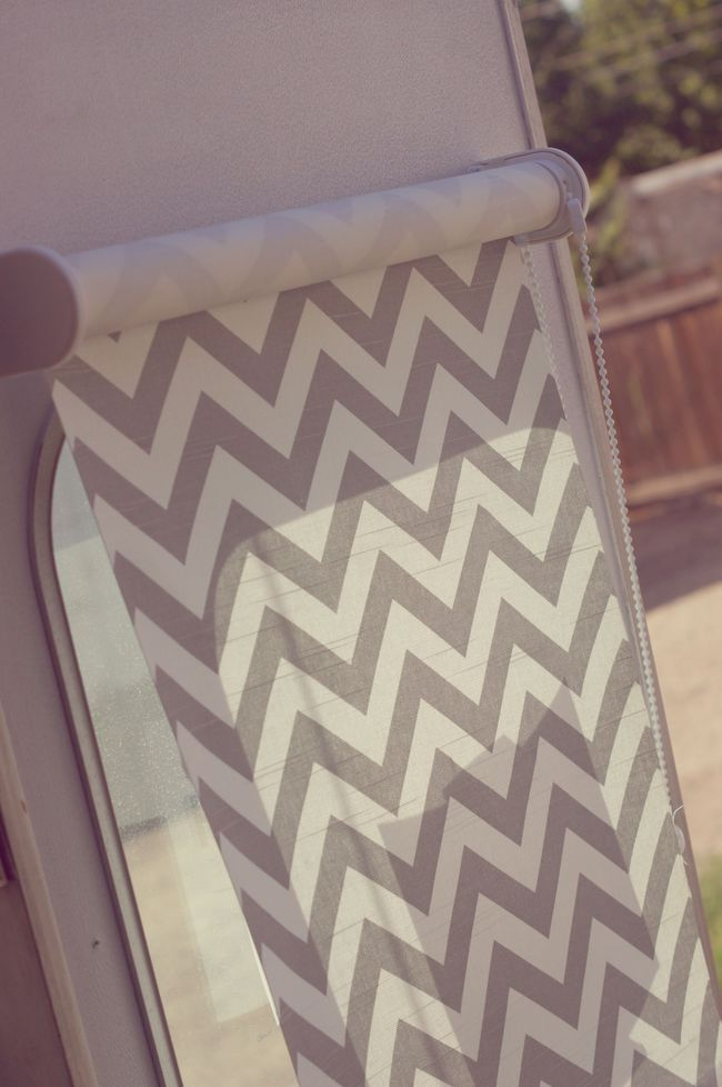 I covered the front with the same chevron fabric that was used for the throw pillows/curtains. I used a 3M adhesive spray and adhered the fabric to the blind, and I did the same thing over the door window http://www.selectblinds.com/