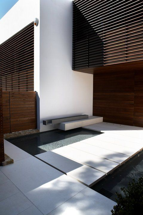 Private House in Greece by Zege Architects, patio with elegant stepping stones & bench-fountain _