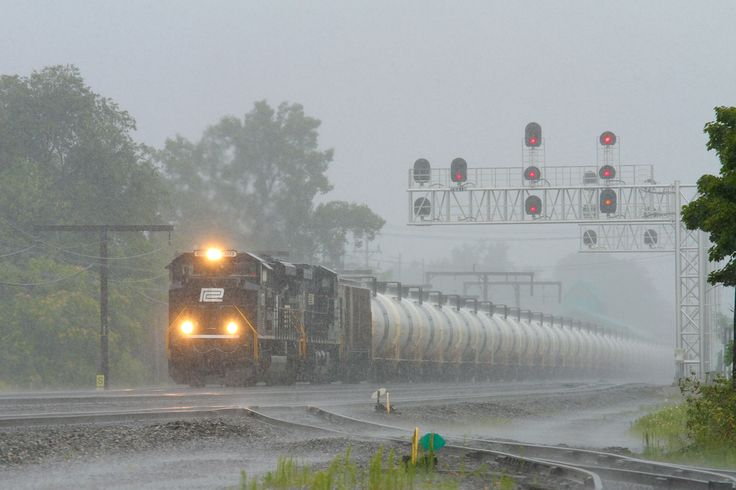 Norfolk Southern' s Penn Central heritage locomotive pulls a string of tank cars through a driving rainstorm in Cleveland, Ohio, on a line of track once operated by Penn Central.  April 2016 Calendar photo by Roger Durfee (utility brakeman in Cleveland) www.nscorp.com