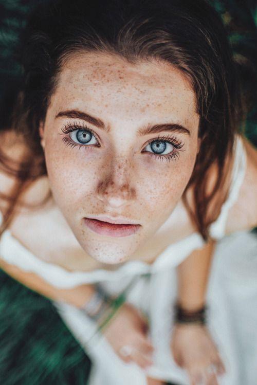 uneven light skin, freckles, long black eyelashes, dark brown hair, blue green eyes, long lips