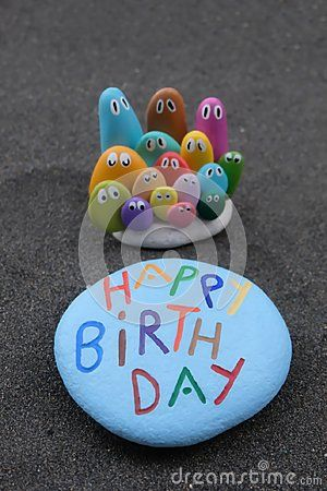 Happy Birthday message with colored pebbles and stones over black volcanic sand