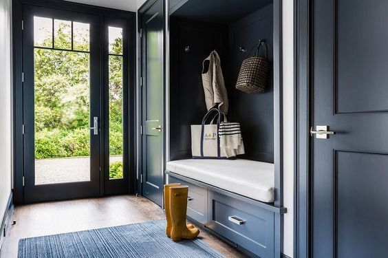 Dark blue mudroom features a dark blue built in bench fitted with drawers placed under a dark blue backsplash lined with hooks flanked by dark blue closet doors.