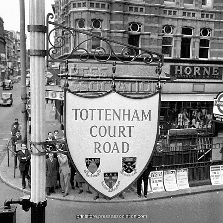 Tottenham Court Road - 1963 The new shield-shaped road sign, costing 300 which hangs at St. Giles Circus at the junction with Tottenham Court Road, London.