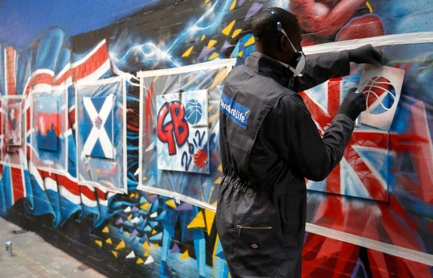 Eric Boateng of the Standard Life Great Britain Men's Basketball team paints a graffiti canvas during a players day at Unity Radio HQ, on July 16, 2012 in Manchester, England.