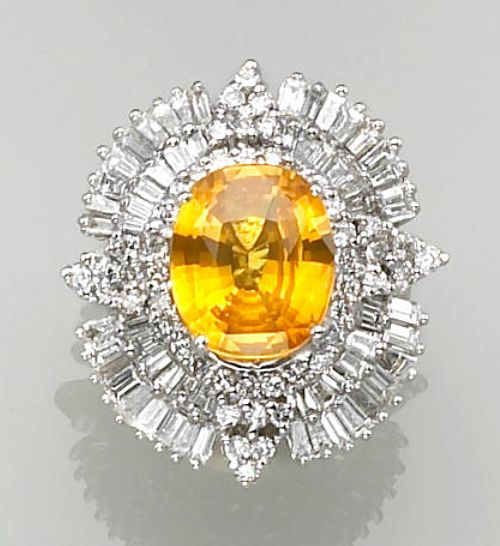 An orangy yellow sapphire, diamond and fourteen karat white gold ring  centering an oval-shaped orangy yellow sapphire, framed by quadrants of round brilliant and baguette-cut diamonds