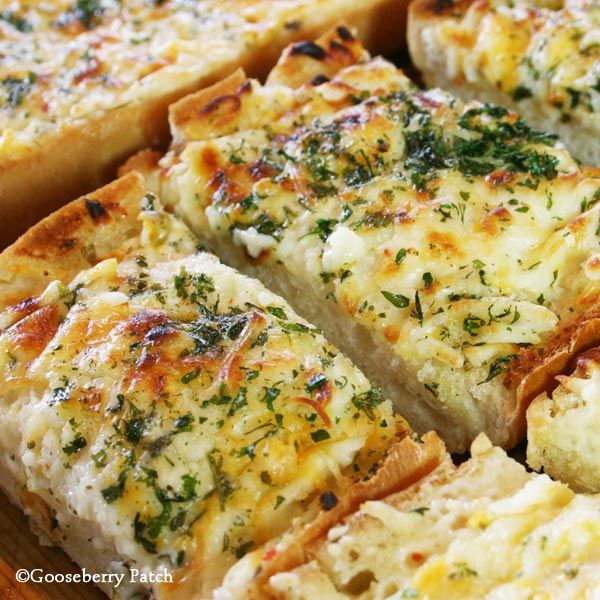 Bubbly Cheese Garlic Bread    1/2 c. butter, softened  1 to 2 cloves garlic, crushed  1/2 to 1 c. creamy Italian salad dressing  1 loaf Italian bread, halved lengthwise  2 c. shredded Cheddar, mozzarella or Monterey Jack cheese  2 t. dried parsley